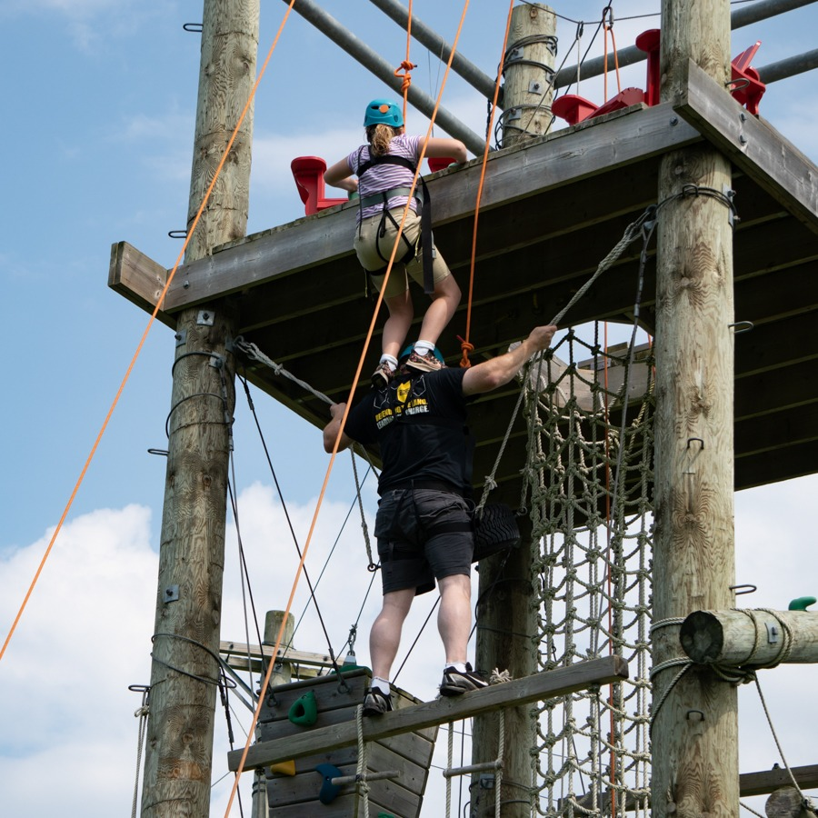 A daughter stands on her fathers shoulders climbing to the top of an adventure element.