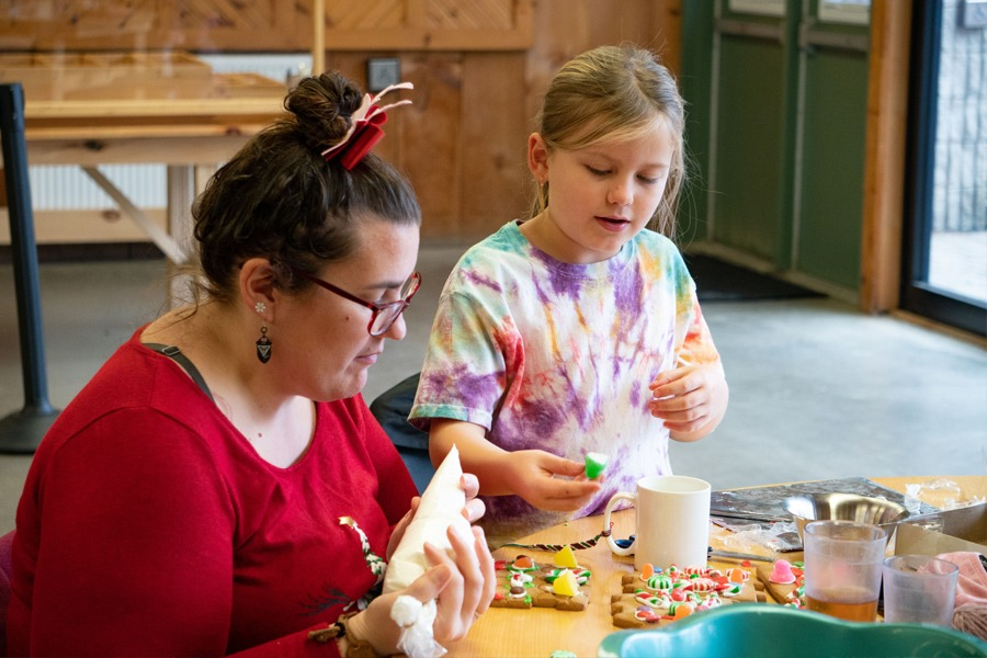 An adult and child work together at a table decorating gingerbread cookies with icing and candy.