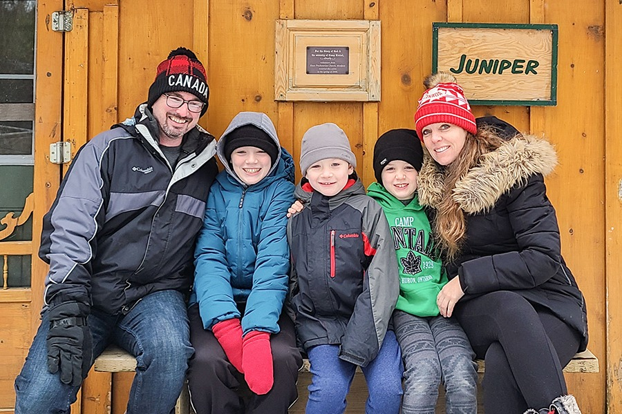 A family wearing winter jackets and winter hats sit smiling on the bench in front of the Juniper cabin.