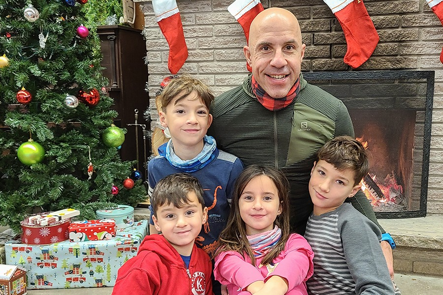 The Radan family sits smiling in front an indoor fireplace next to a decorated Christmas tree at Camp Kintail.