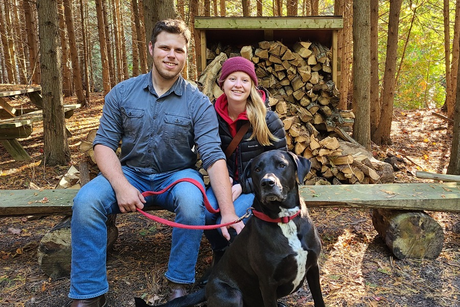 Staff members, camp names Arctic and Banana, sit on a wooden bench in front of cedar trees smiling with their dog Burt!