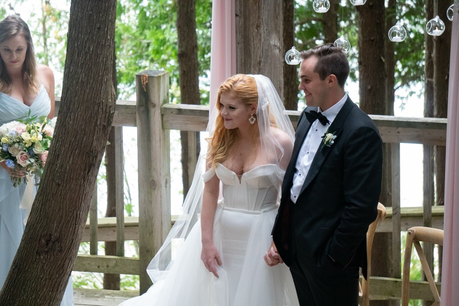 Isabelle and James stand smiling hand in hand at the outdoor Chapel.