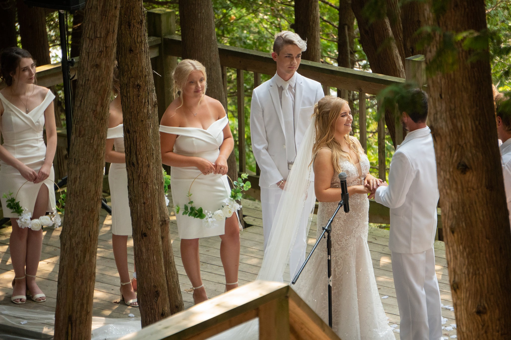 Wedding couple Jodi and Mackenzie stand hand in hand smiling on the outdoor Chapel stage with their wedding party dressed in white surrounding them.
