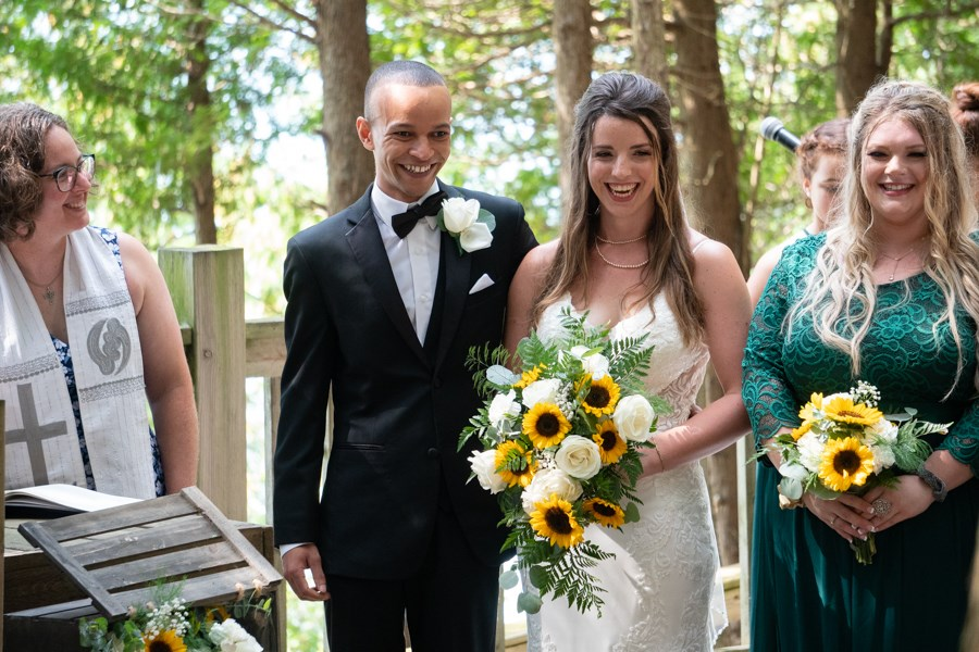 Wedding couple Lisa and Marley smile at the camera in the outdoor Chapel with Theresa McDonald-Lee beside them as their officiant.