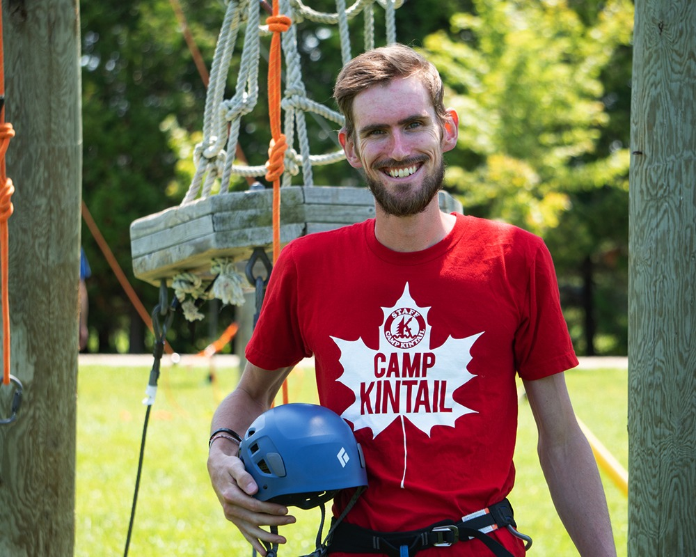 A young man stands in front of a ropes course holding a helmet.