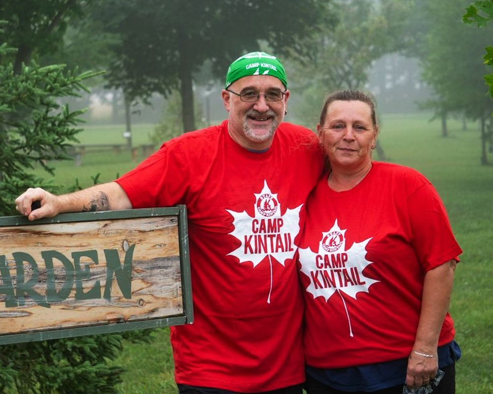 Mark and Tracy, two adults stand smiling beside a sign reading